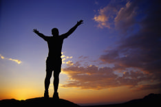 This image shows a man rejoicing atop a mountain. Finding a job can seem like a massive challenge but by improving your skills you too can be successful